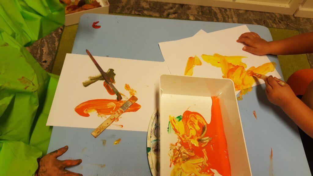 Barn som målar i orange på Vallare Öppna förskola
