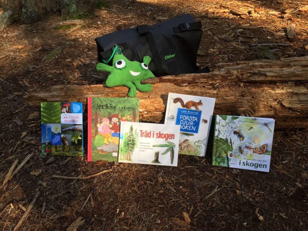 Ute-Ugo, en tygfigur i grönt, lärvän, ute i naturen med böcker,osmos öppna förskola