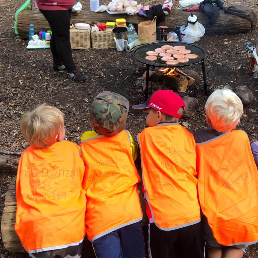 Barn i orangea västar står på knä och väntar på mat vid stekbord utomhus i skogen